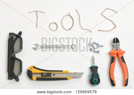 Set of tools containing screwdriver, pliers, wrench, cutter, glasses, twine and screws arranged on a white background in top view. Thread twine making words TOOLS.