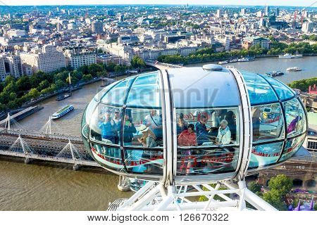 LONDON UK - JUNE 6 2015: Unidentified people inside London Eye cabin on cityscape background. London Eye is a giant Ferris wheel situated on the banks of the River Thames