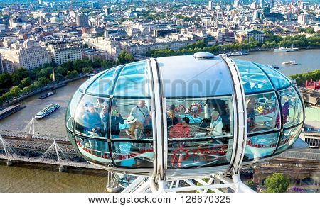 LONDON UK - JUNE 6 2015: Unidentified people inside London Eye cabin on blue sky background. London Eye is a giant Ferris wheel situated on the banks of the River Thames