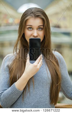 Young brunette woman covers her face screen smart phone, indoor