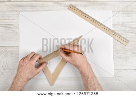Work place of constructor with triangle centimeter ruler and simple centimeter ruler. Close-up man hands  during measuring process.