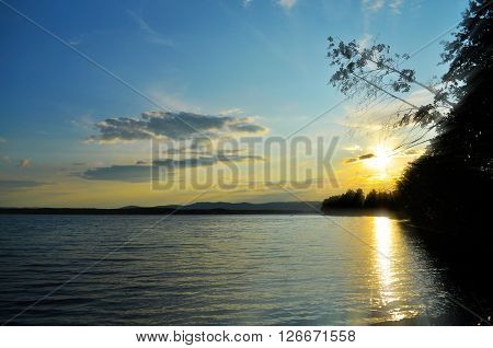 Summer silhouette landscape - sunset over the Ural mountains and Irtyash lake in Southern Urals Russia