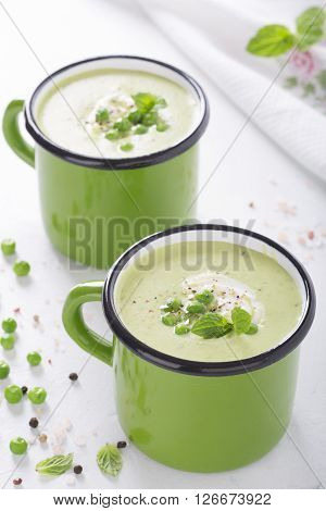 Cream of green peas in green cups on a white background close-up