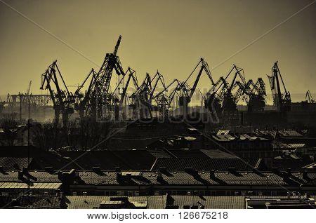 Industrial landscape in sepia tones - birds eye view of cargo crane in port of Saint-Petersburg Russia