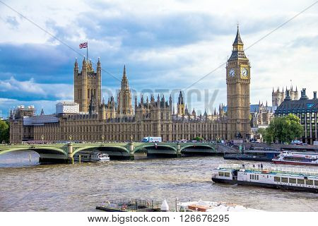 LONDON UK - JUNE 6 2015: Tourist pleasure boat on the River Thames at summer evening on cityscape of London  with houses of Parliament, Big Ben , Westminster Abbey and Westminster bridge and cloudy sky background
