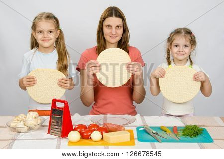 Mum With Two Little Girls Sitting In A Row At The Kitchen Table And A Hand-held Pizza Bases