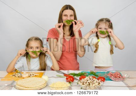 Young Housewife With Two Daughters Having Fun Holding Sprig Of Parsley As A Mustache At The Kitchen