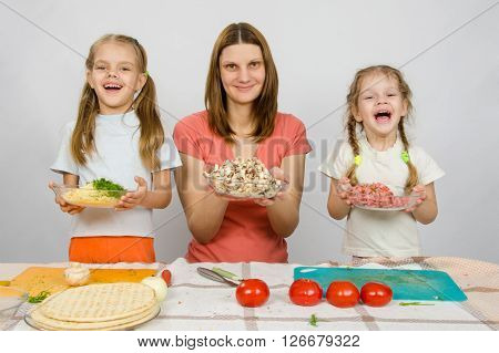 Mother With Two Daughters Happily Holding A Plate With Sliced Products For Pizza