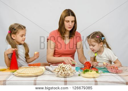 Mom Shows Two Young Daughters At The Kitchen Table As The Cut Tomato Pizza