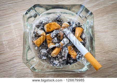 burn cigarette in a full ashtray on woody background