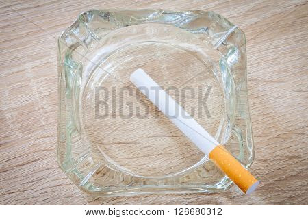 a cigarette in an ashtray on woody background