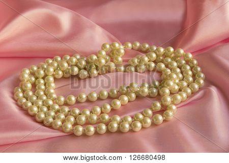 Pearl Necklace on delicate Pink silk background
