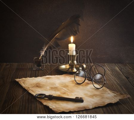 Vintage letter concept (candles, glasses, pen and old paper)