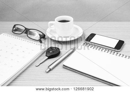 coffee and phone with car keyeyeglassesnotepadcalendar on wood background black and white tone