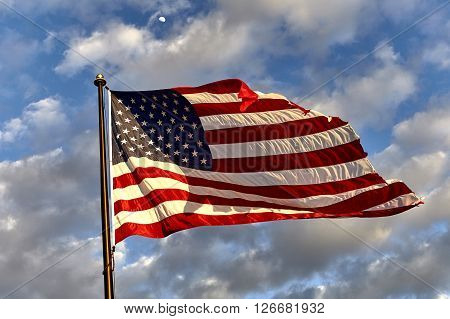 Weathered American flag on flagpole waving in the wind against clouds blue sky and the moon