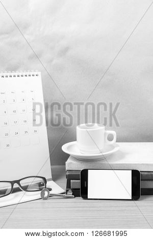 coffee and phone with key eyeglasses stack of book calendar on wood background black and white tone