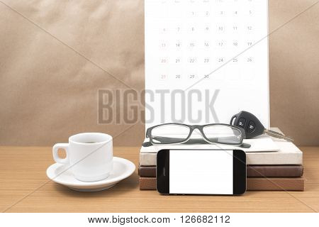coffee and phone with car key eyeglasses stack of book calendar on wood background
