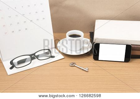 coffee and phone with key eyeglasses stack of book calendar on wood background