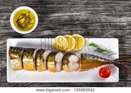 Slices of Smoked fish Mackerel or Scomber on a white rectangular dish with cherry tomato sliced lemon and rosemary on an old wooden table small bowl with olive oil studio lights top view