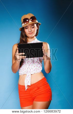Technology internet modern lifestyle concept. Young summer girl using tablet computer reading. Latin female with e-book reader touchpad pc.