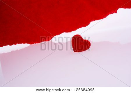 Heart near torn red paper on a white background