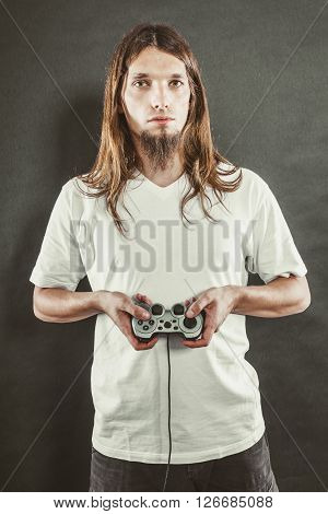 Addiction and dependency concept. Young man with pad joystick playing games. Male addicted to console videogames.