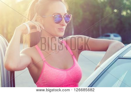 Attractive young fit woman wearing sunglasses standing by her car smilling showing v-sign, victory gesture or peace outdoors portrait