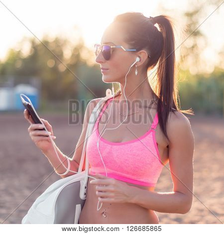 Athlete woman listening music looking at smartphone after workout in nature outdoors portrait summer evening on the beach summer holidays and vacation healthy lifestyle.