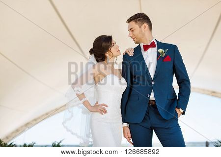 Young wedding couple enjoying romantic moments looking to each other outside against modern buildings