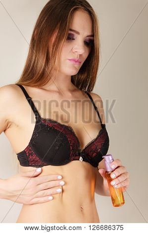 Woman model applying moisturizing body oil lotion. Girl in underwear with moisturizer bottle. Skincare.