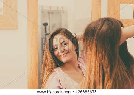 Woman Taking Care Of Her Long Hair In Bathroom