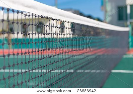 Outdoor empty tennis court with ready net