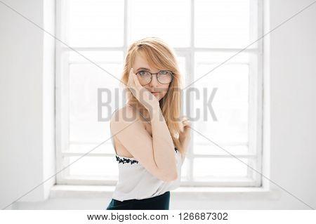 Sexy modern woman. Studio shot against window. Copy space.
