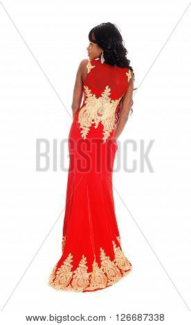 A gorgeous African American woman standing in a long red evening dress with gold embroideries and long black hair isolated for white background.