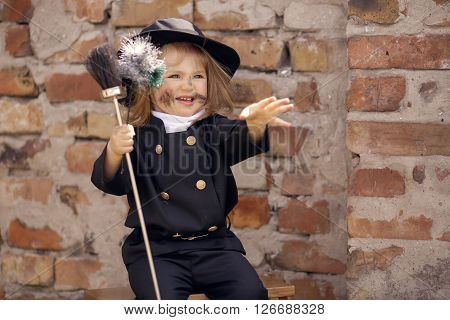 Girl as a chimney sweep against brick wall.