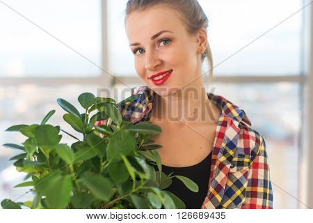 Close-up portrait of a young beautiful woman, holding decorative plant, smiling, looking at camera.
