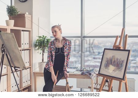 Female painter standing in workshop, watching at drawing attentively, holding paintbrush. Artist looking on picture concentrated, front view portrait
