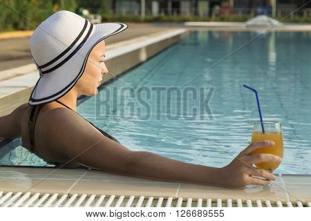 Beautiful blond wearing a hat sitting on the edge of a swimming pool and holding a glass of an orange juice