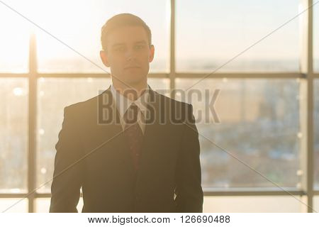 Close-up portrait of a young handsome businessman, looking seriously at camera, standing in light office over the large window background