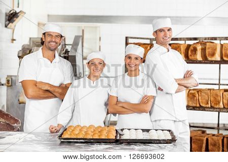 Confident Male And Female Baker's Standing At Table