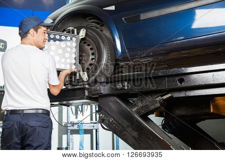 Mechanic Adjusting Wheel Aligner On Car