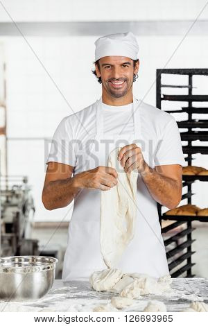Smiling Mid Adult Baker Holding Dough At Table