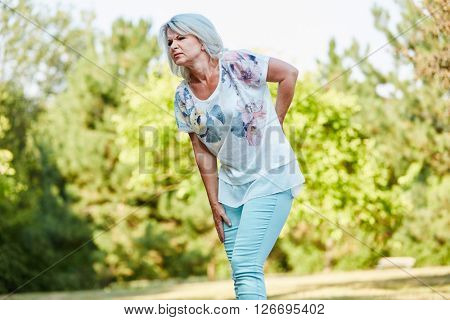 Old woman with back pain while walking in the nature in summer