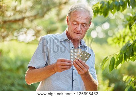 Senior man tablets on his hand in the nature
