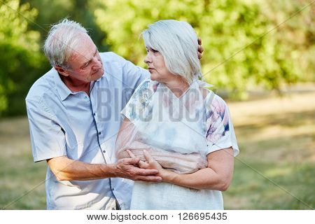 Man comforting old woman with broken arm in a loop