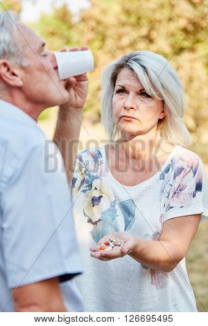 Woman helps old man to take his medicine and he drinks water