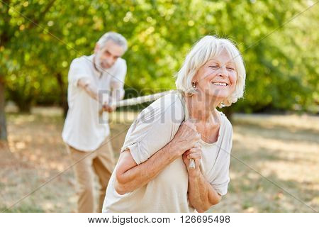 Two seniors playing tug of war with a rope in the nature