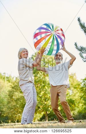 Happy senior couple throwing a big ball on their holiday