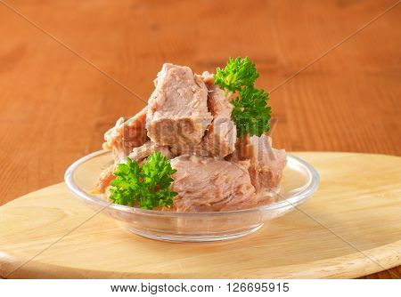 bowl of canned tuna with parsley on wooden cutting board - close up