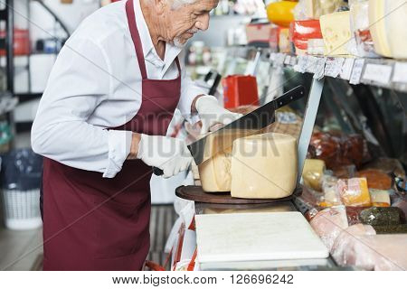 Salesman Slicing Cheese With Double Handled Knife At Counter